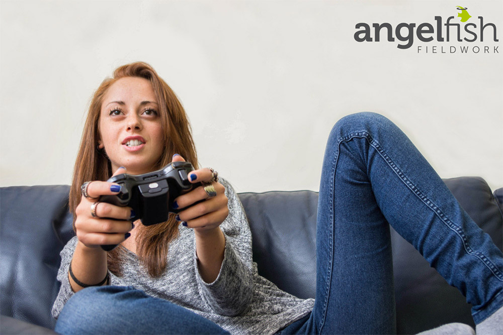 Woman sat on a sofa playing a video game with the Angelfish Fieldwork logo in the top right corner