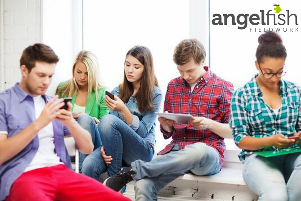 Group of young people sat together looking at their phones, overlayed with the Angelfish Fieldwork logo