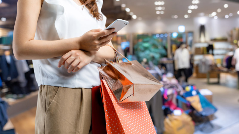 Woman with shopping bags looking at her phone