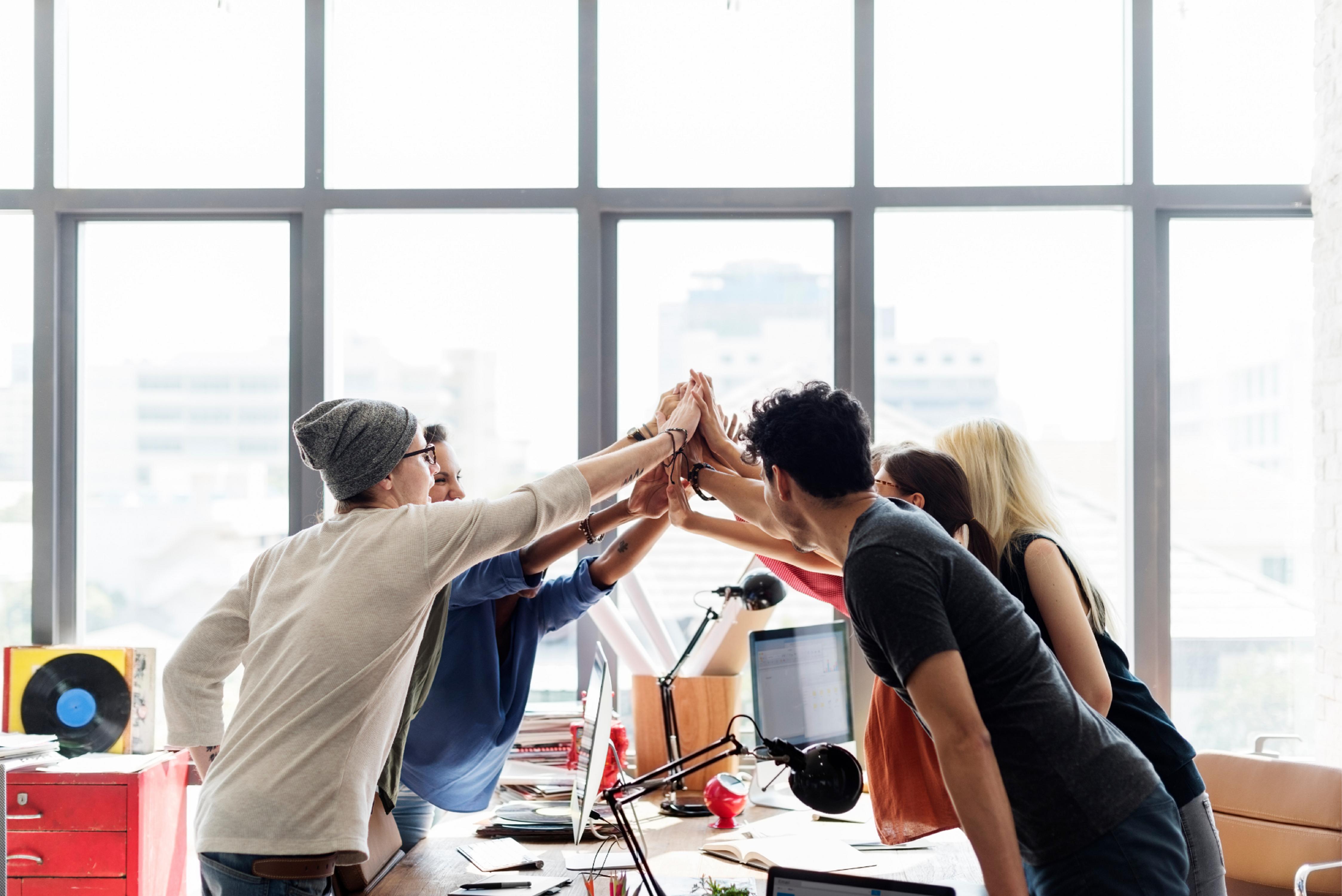 An office team doing a group high five