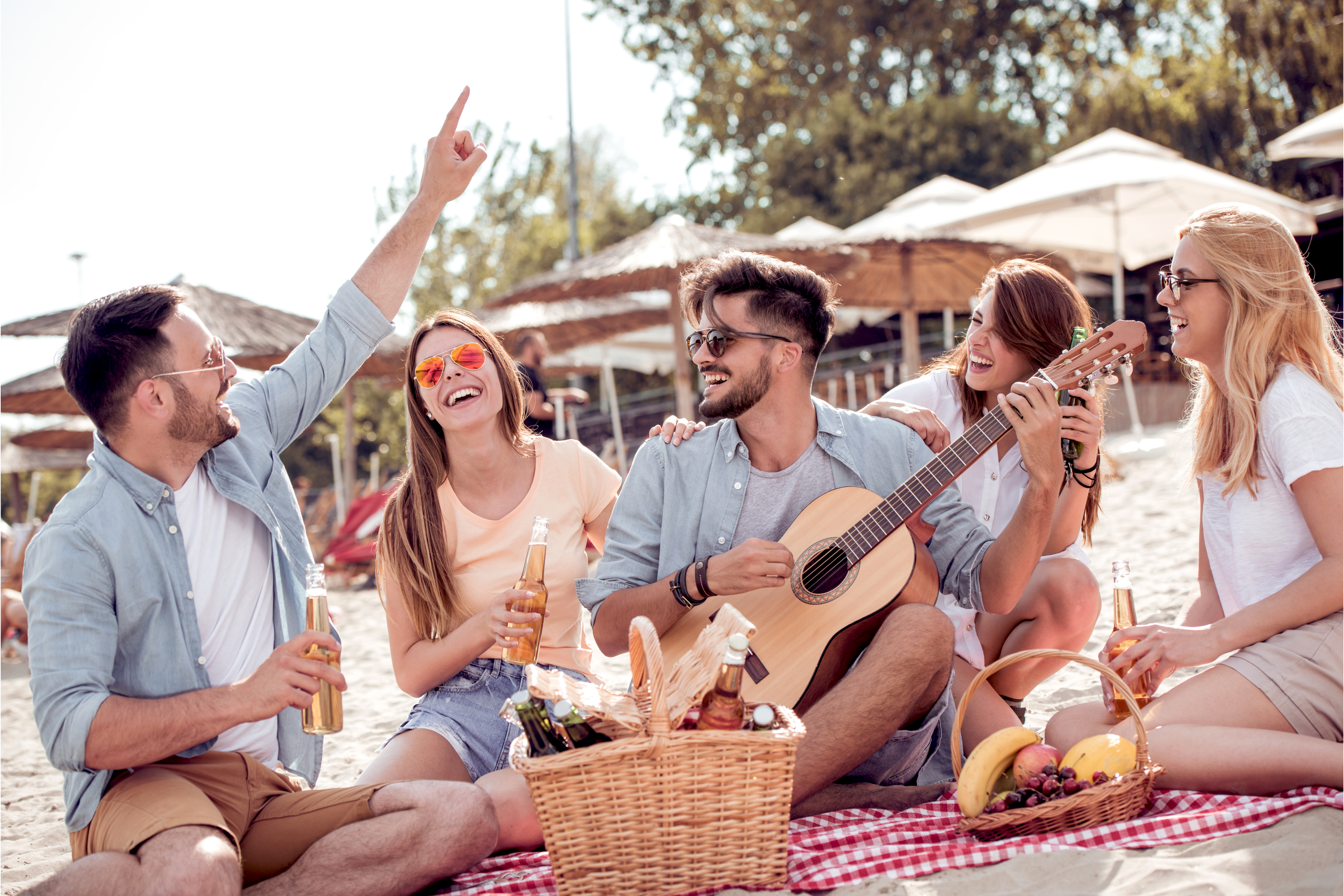 Group of young people drinking cider outdoors at a picnic, demonstrating the benefits of online communities in market research