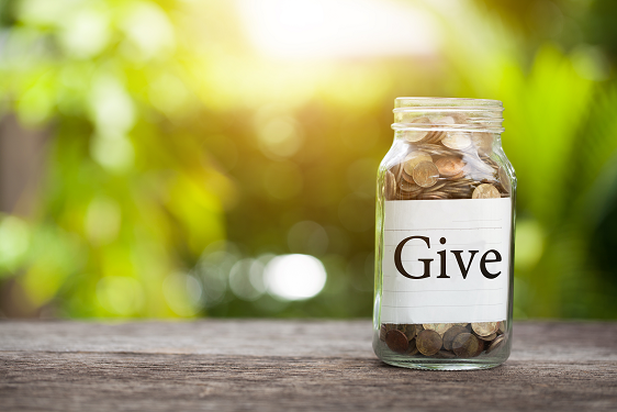 """A jar full of coins on a table in front of a blurred green background with a label saying """"Give,"""" representing charity market research"""