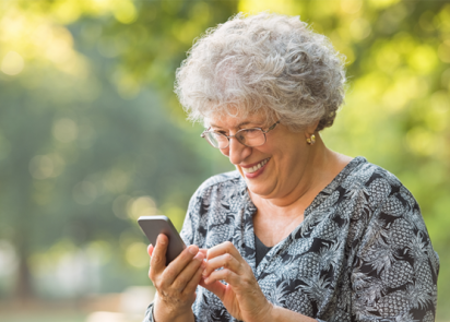 A smiling senior woman in the garden using her smartphone as part of market research for charities